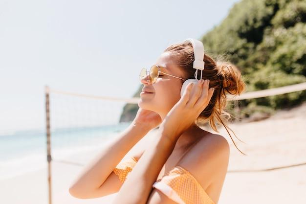 Close-up ritratto di gioiosa donna abbronzata rilassante con la musica preferita in spiaggia. colpo esterno del modello femminile sorridente in cuffie che trascorrono del tempo al resort.