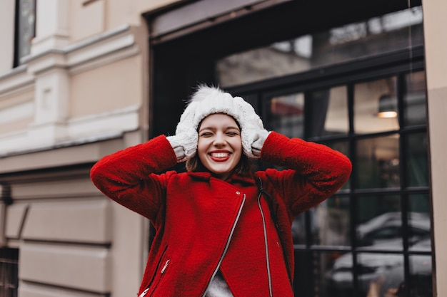 Close-up portrait of joyful woman with red lipstick, laughing with closed eyes. girl in warm coat, hat and mittens touches her head.