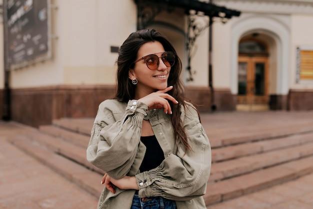 Ritratto del primo piano della ragazza castana di risata che cammina sul fondo della città. donna felice in occhiali da sole e vestito che cammina all'aperto. immagine di bella donna alla moda sulla strada il giorno di primavera