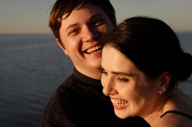 Close-up portrait of a laughing couple in love on the background of the sea in the sunset lighting.