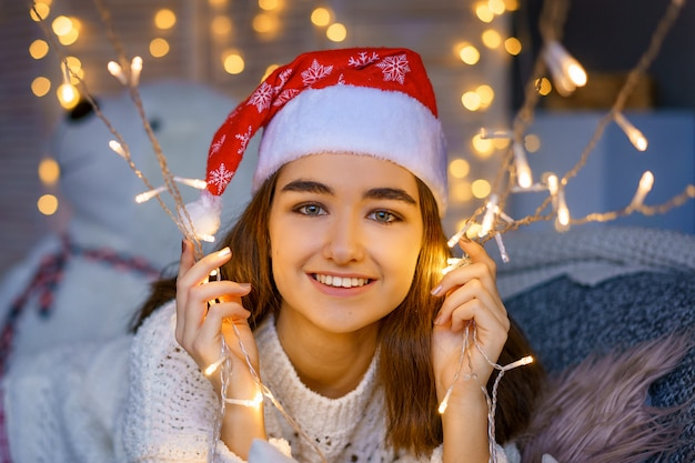 Close-up portrait of a laughing cute young woman with a santa hat on her head with garlands in her hands