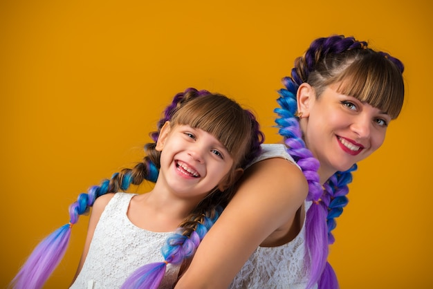 Close-up portrait of laughing positive mom and daughter with the same colored hairstyles and white dresses on a yellow wall