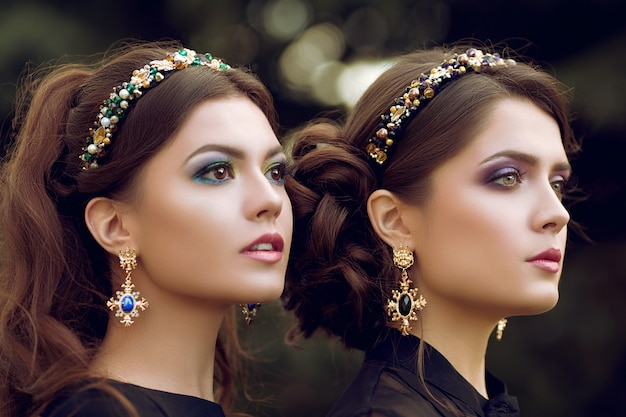 Close-up portrait of life image of two young beautiful women. edgy, stylish jewelry, fashionable, trendy makeup, gold earrings with stones hoop on the head with precious stones.