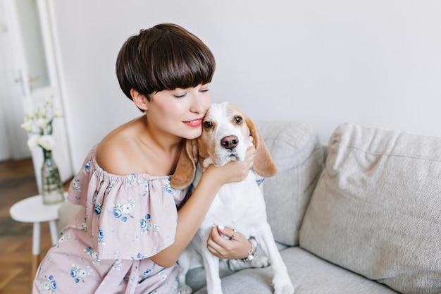 Ritratto del primo piano della ragazza leggermente abbronzata in posa che abbraccia il suo animale domestico sul divano