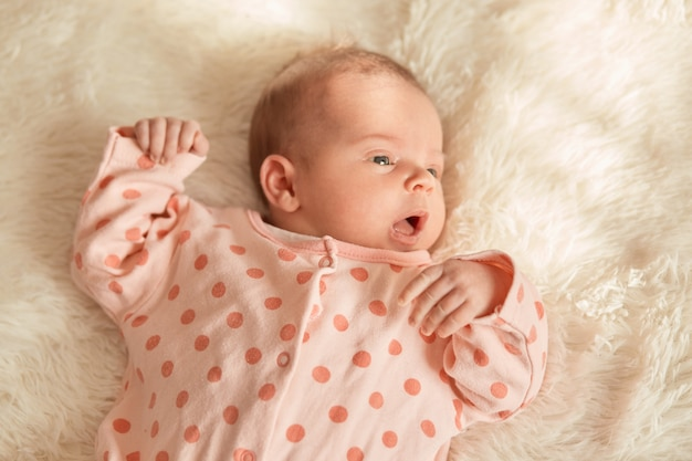 Close up portrait of little baby lying in bed on white fluffy, new born baby looking away with opened mouth, charming kid wearing sleeper with polka dots.