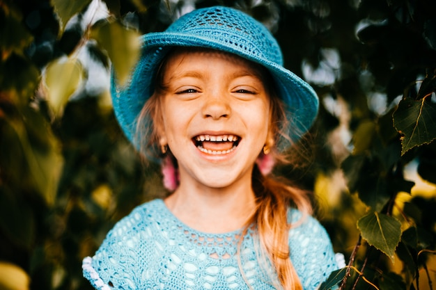 Close up portrait of little beautiful cutie princess girl with emotional face fooling and making faces. smiling and laughing kid. monkey on abstract background in autumn. orange fall tree leaves