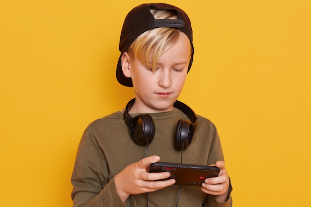 Close up portrait of little blond boy wearing green shirt