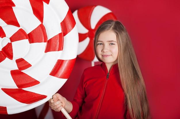 クローズアップの肖像画赤い背景に巨大なクリスマスのお菓子を持つ小さなブロンドの女の子