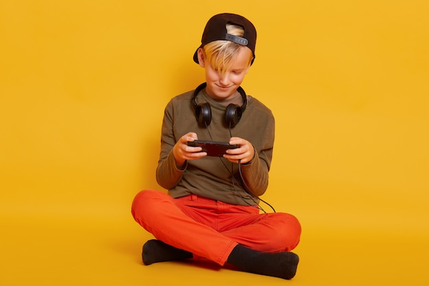 Close up portrait of little blond guy wearing casual clothing, posing with headphones around neck, playing online video games via mobile phone, looks concentrated, isolated on yellow.