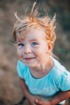 Close up portrait of little blonde girl with blue eyes outside with tousled hair and smiling dirty face. childhood in the country, wind in the hair.