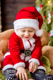 Close-up portrait of a little boy dressed as a red santa claus, playing by a stone fireplace with bright garlands
