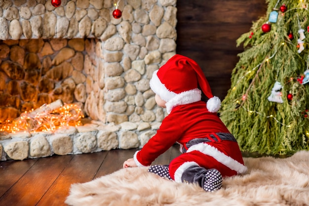 Close-up portrait of a little boy dressed as a red santa claus