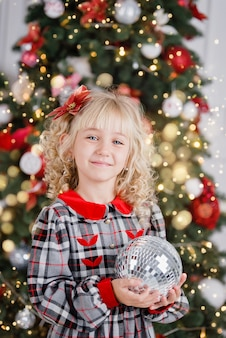 Close up portrait of little cute smiling girl near decorated christmas tree.