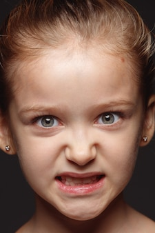 Close up portrait of little and emotional caucasian girl. highly detail photoshot of female model with well-kept skin and bright facial expression. concept of human emotions. angry, looking at camera.