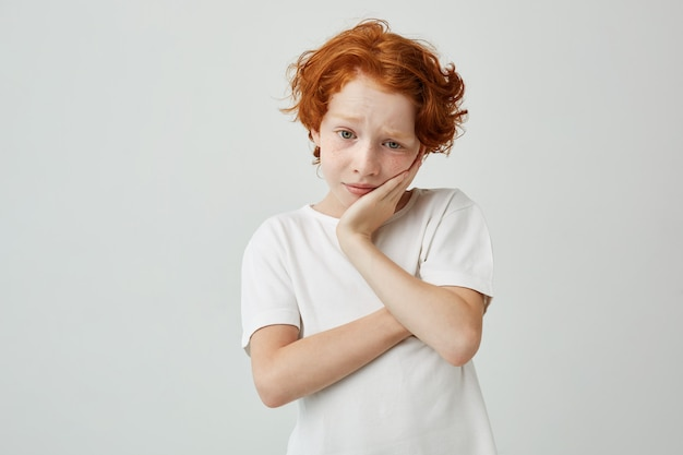 Close up portrait of little ginger boy holding head with hand looking aside with sad expression