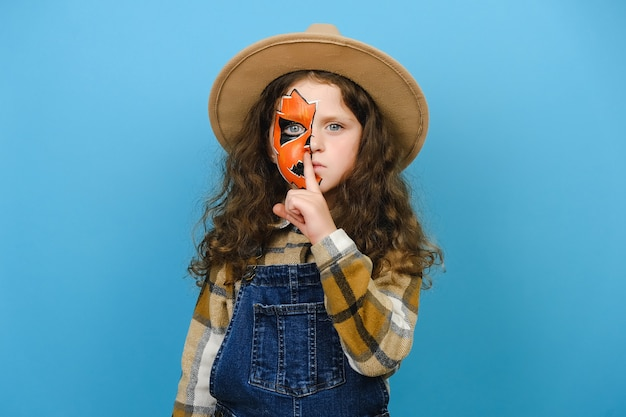 Close up portrait of little girl child with halloween makeup mask wear hat and shirt, say hush be quiet finger on lip shhh gesture isolated on blue background studio. celebration holiday party concept