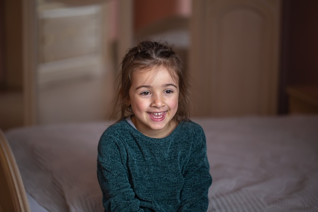 Close-up portrait of a little girl in her room on the bed on a blurred background.