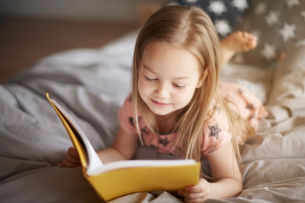 Close up portrait of little girl reading in bed