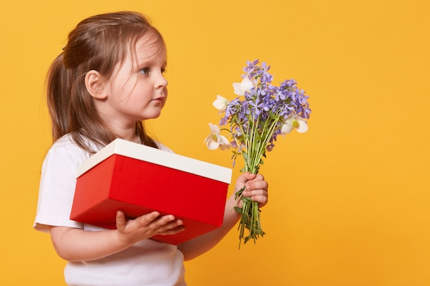 Close up portrait of little girl with red gift box and bouquet of blue florets