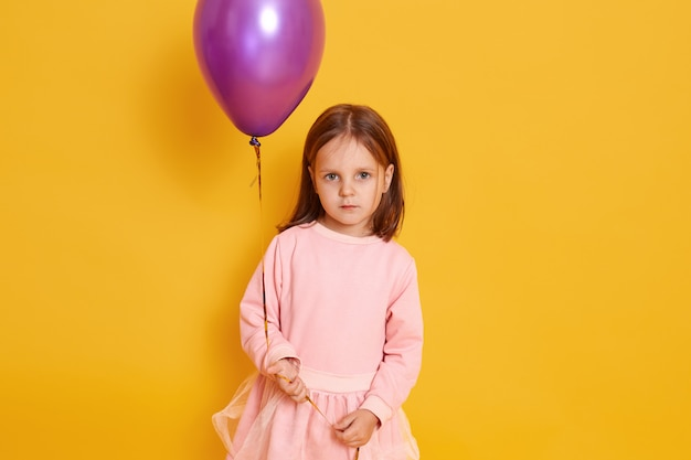 Close up portrait of little girl with violet balloon posing isolated on yellow, kid wearing rosy dress, having dark straight hair, holding her birthday present