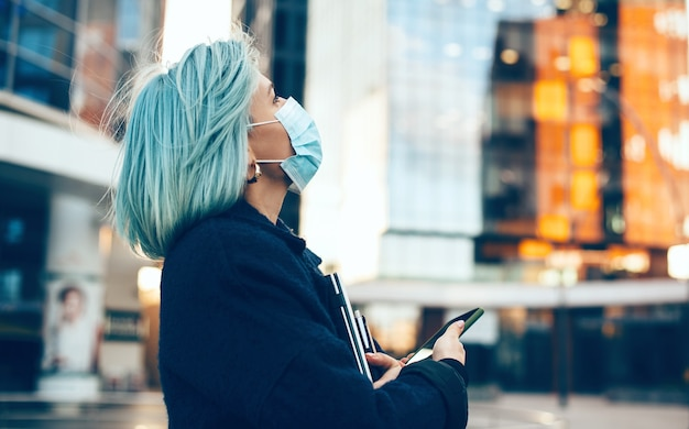 Close up portrait of a looking up woman with blue hair wearing a anti flu mask while holding a laptop and her phone