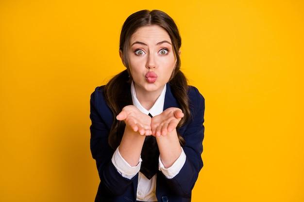Close-up portrait of lovable amorous lovely schoolgirl sending air kiss