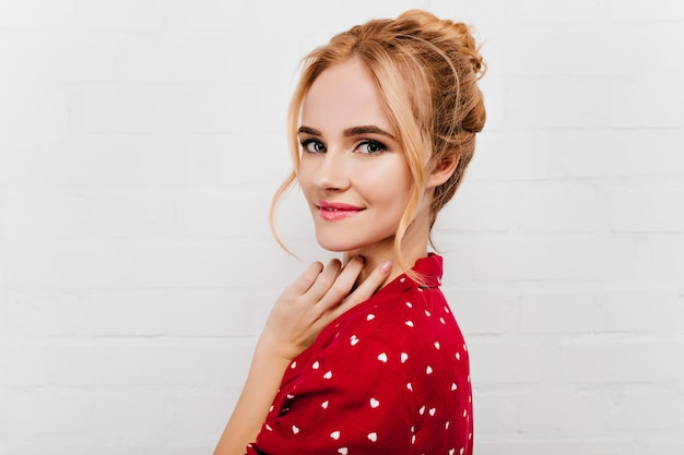 Close-up portrait of lovable blue-eyed girl isolated on white wall. cheerful female model in red pajama looking