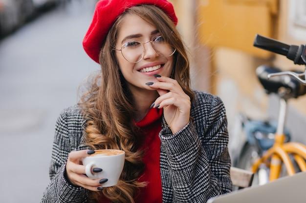 Ritratto del primo piano della giovane signora adorabile con il manicure nero che posa con la tazza di caffè caldo