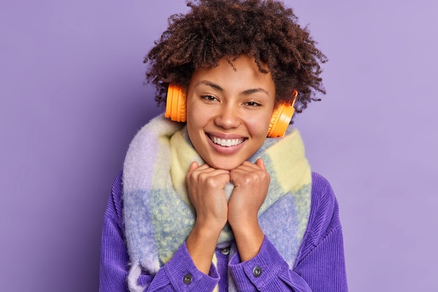 Close up portrait of lovely dark skinned millennial girl keeps hands under chin smiles broadly enjoys leisure time wears winter clothes listens pleasant music.