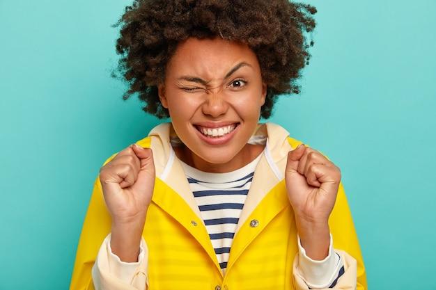 Close up ritratto di bella donna energica ammicca gli occhi, solleva le sopracciglia, stringe i pugni con successo, si sente molto felice