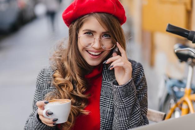 Ritratto del primo piano della bella ragazza francese con il manicure nero che osserva con il sorriso interessato