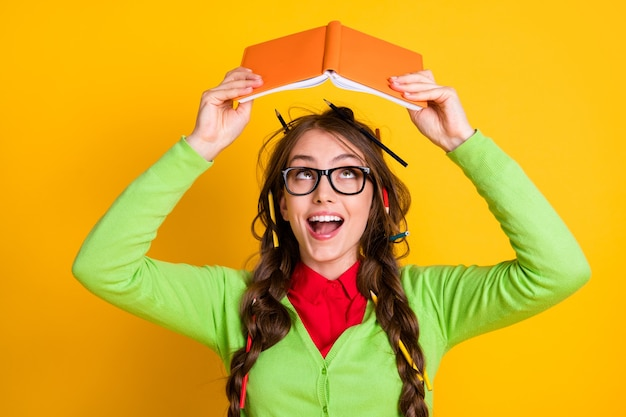 Close-up portrait of lovely funky clever cheerful teenage girl reading book literacy isolated over bright yellow color background