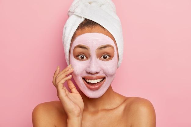 Close up ritratto di bella felice giovane donna applica la maschera facciale sulla carnagione, utilizza argilla nutriente per il ringiovanimento, indossa un asciugamano bianco avvolto sulla testa