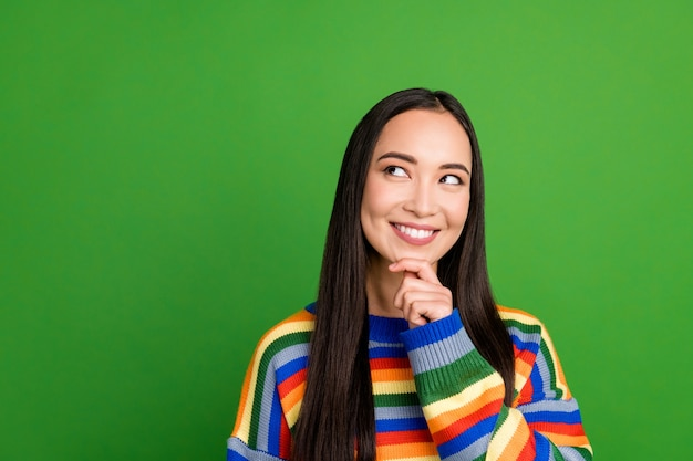 Close-up portrait of lovely pensive cheerful girl wearing striped pullover creating solution copy space isolated over green color background