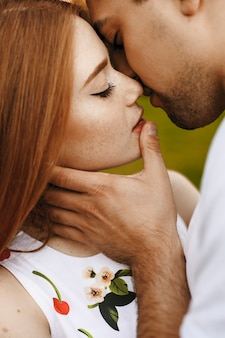 Close up portrait of a lovely red haired female with freckles kissing with her man with closed eyes closed while man is touching her on the lips.