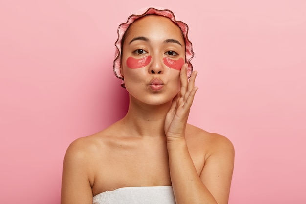 Close up portrait of lovely woman has natural beauty, keeps lips folded for kissing someone, wears waterproof bathcap, touches cheek, enjoys freshness of skin, has eye patches on face, poses indoor