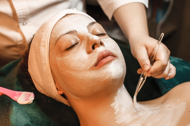 Close up portrait of a lovely woman relaxing after work in wellness spa center while doing mask on her face and body.