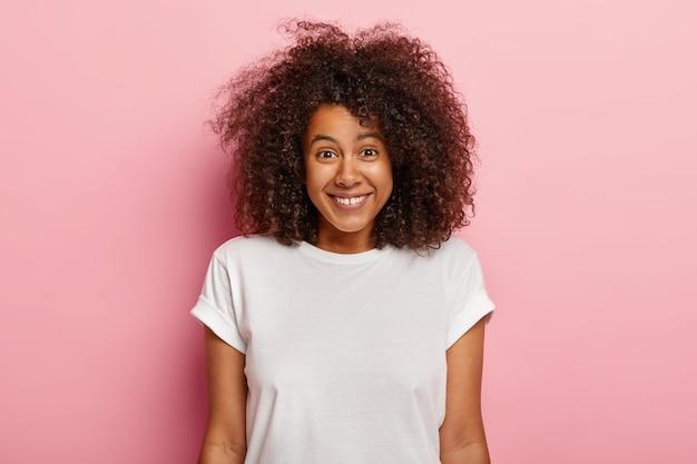 Close up ritratto di bella giovane donna afroamericana sorride positivamente, gode di scene divertenti, è divertito, ridacchia per scherzo esilarante, ha capelli voluminosi ricci scuri, indossa abiti casual