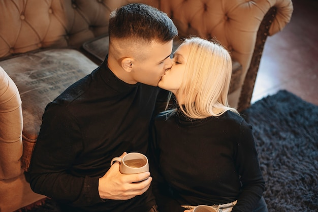 Close up portrait of a lovely young couple kissing on the floor at home while drinking hot coffee leanin on a sofa.