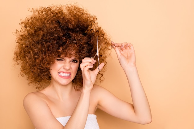 Close-up portrait of mad crazy girl cutting dry split damaged ends curls