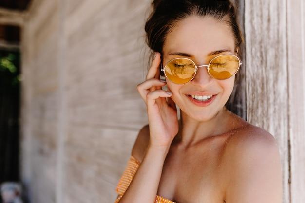 Ritratto del primo piano della magnifica donna europea sorridente con gli occhi chiusi e toccando il suo viso. modello femminile ispirato in occhiali arancioni alla moda in posa sulla parete di legno.