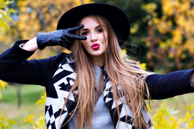 Close-up portrait of magnificent lady in black hat fooling around during autumn photo shoot. funny young lady in elegant gloves spending time in park in september day.