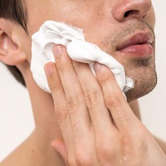 Close up portrait of man applying shaving foam
