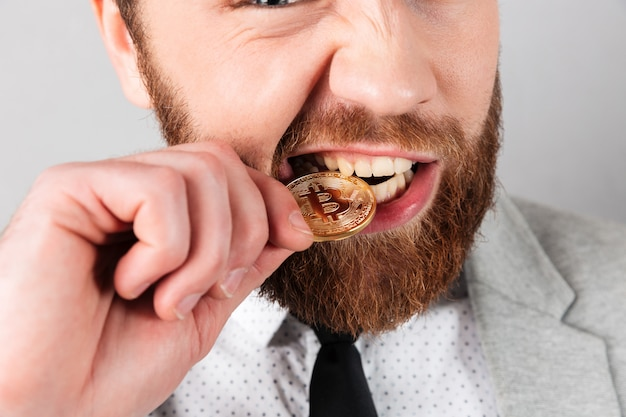 Close up portrait of a man biting golden bitcoin