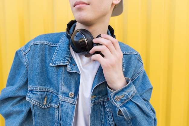 Close-up portrait of a man in a denim jacket and a wireless headset on the neck.