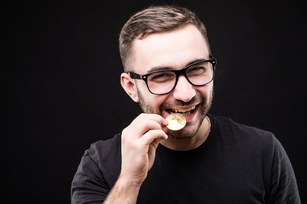 Close up portrait of a man in glasses biting golden bitcoin isolated over black