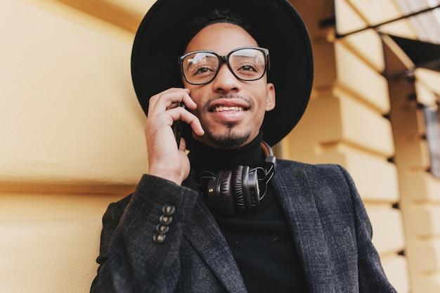 Ritratto del primo piano dell'uomo in giacca grigia e camicia nera che chiama amico. foto all'aperto del ragazzo alla moda in bicchieri scintillanti in piedi sulla strada con lo smartphone.