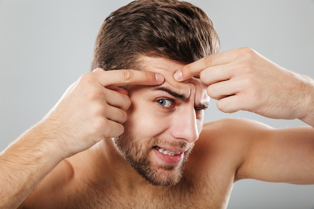 Close up portrait of a man squeezing pimple