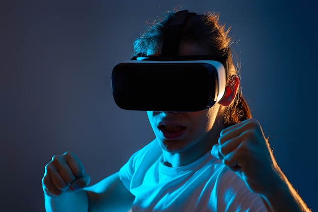 Close-up portrait of man using glasses of virtual reality on dark blue background. neon light.