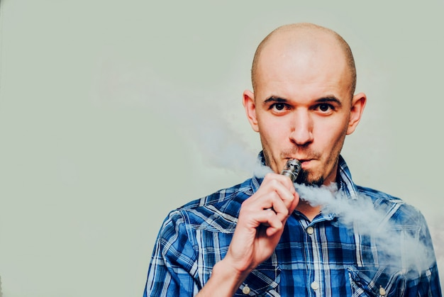 Close up portrait of a man vaping.